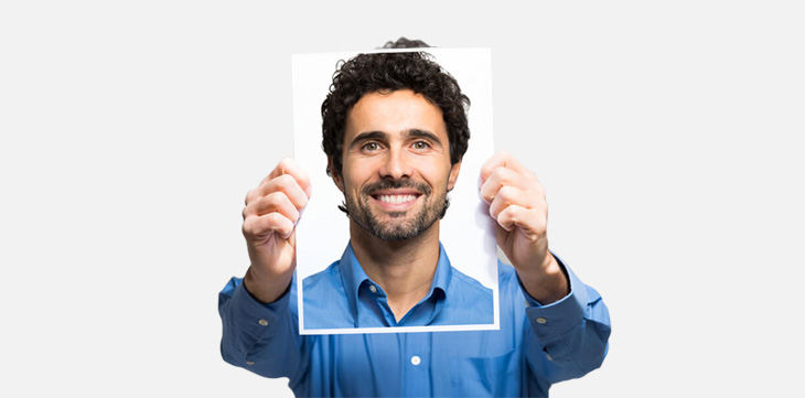 man holding better photo of himself in front